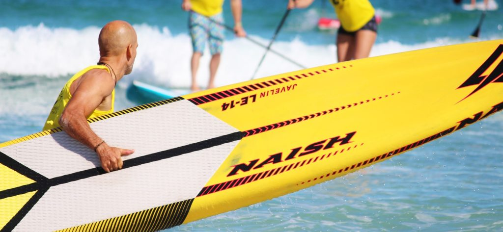 Welches SUP Board kaufen? Ein Mann mit einem längeren SUP board steht am Strand. Da er ein längeres SUP board gekauft hat, erreicht er eine schneller Geschwindigkeit.